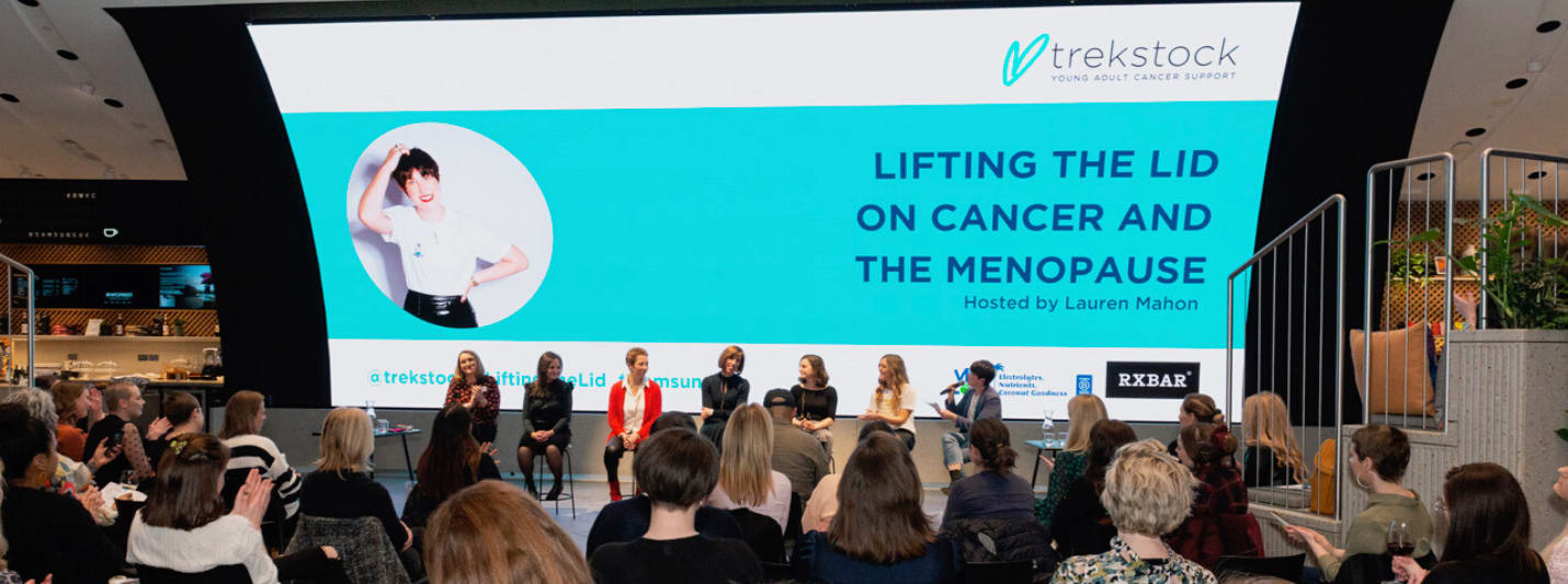 A picture of the Lifting the Lid on Cancer and the Menopause event at Samsung KX. A panel of women sit on stools in front of a large screen. A large audience are sitting on chairs watching them.