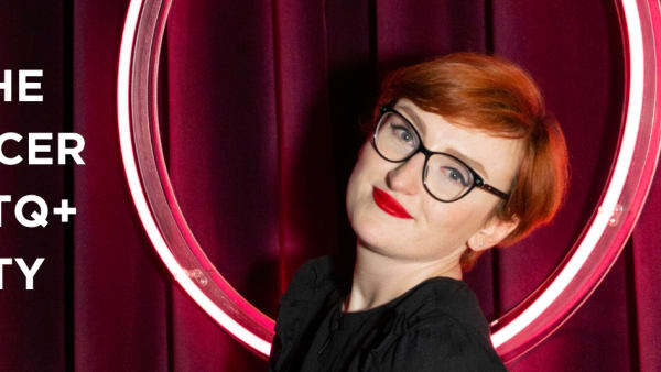 Close up of Emma McAuley. She is in front of a maroon velvet curtain. She has short red hair and is wearing black glasses and red lipstick.